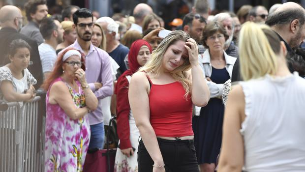 A member of the public attends a moment of silence for shooting victims near the City Hall in Liege (Geert Vanden Wijngaert/AP)