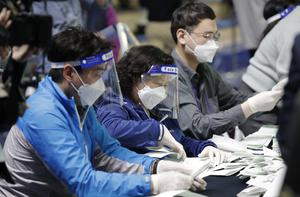 South Korean National Election Commission officials wore personal protective equipment to slow the spread coronavirus (Lee Jin-man/AP)