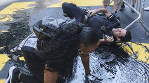An NYPD officer falls during an attempt to detain a protester pouring black paint on the Black Lives Matter mural outside Trump Tower (AP/Yuki Iwamura)