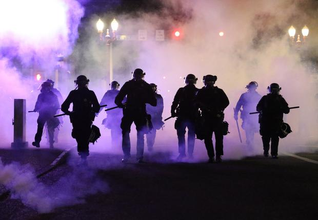 Policemen are enveloped in tear gas as the monitor protests in Portland, Oregon (Dave Killen/The Oregonian via AP)