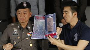 Thai police officers show pictures of tattooed skin during a press conference at Bangpongpang police station in Bangkok (AP)