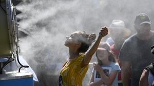 Spectators cool themselves down with a water mist fan during the Australian Open tennis championships (Andy Brownbill/AP)