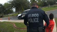 Orlando police officer Dennis Turner leads six-year-old Kaia Rolle away (Orlando Police Department/Orlando Sentinel/AP)