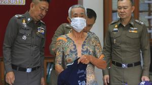 Shigeharu Shirai displays his tattoos at a police station during a press conference in Lopburi, central Thailand (AP)