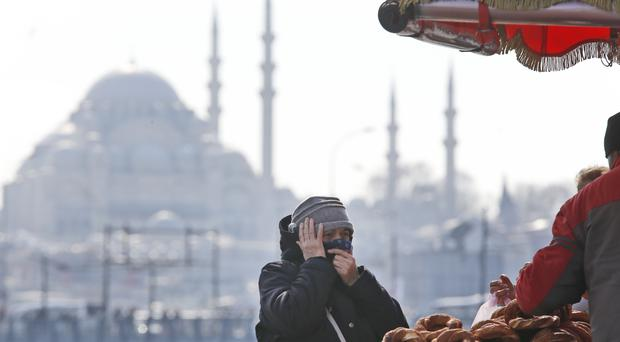 A woman, backdropped by the Suleymaniye mosque, buys simit, a pretzel-like snack, in Istanbul (Lefteris Pitarakis/AP)