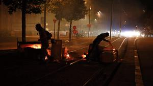 Protesters block a street with rubbish during clashes with police in Nantes (AP)