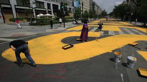 City workers and activists paint the words Black Lives Matter in enormous bright yellow letters on the the street leading to the White House (manuel Balce Ceneta/AP)