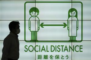 A banner reminding the public of social distancing in Japan (Eugene Hoshiko/AP)