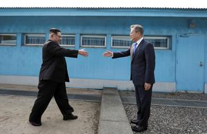 North Korean leader Kim Jong Un prepares to shake hands with South Korean President Moon Jae-in over the military demarcation line in the border village of Panmunjom (Korea Summit Press Pool/AP)