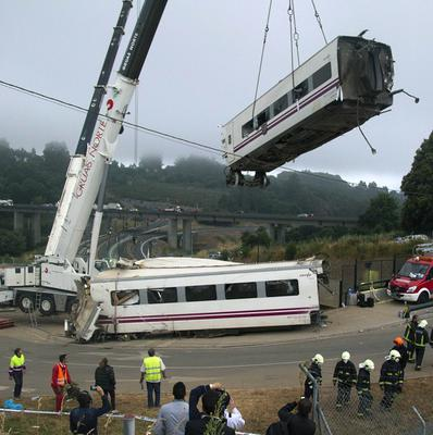 Derailed cars are removed as emergency personnel work at the site of a train accident in Santiago de Compostela (AP)