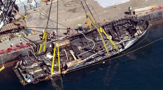 The burned hull of the dive boat Conception is brought to the surface by a salvage team (Brian van der Brug/Los Angeles Times via AP)