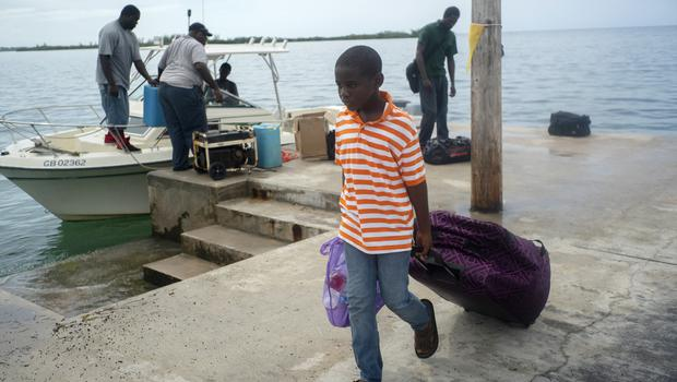 A child pulls his suitcase after being evacuated before the arrival of Hurricane Dorian in Sweeting's Cay, Grand Bahama, Bahamas (Ramon Espinosa/AP)