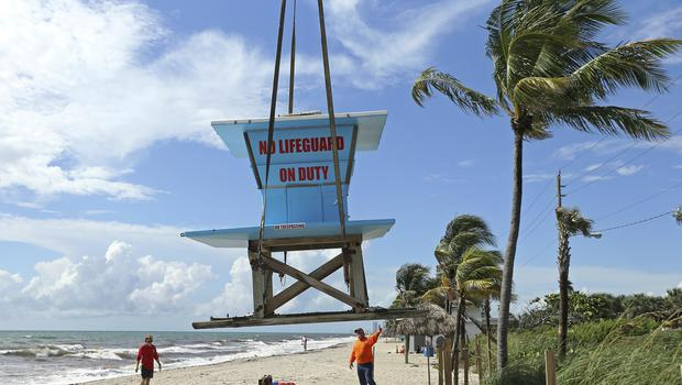Gold Coast Crane workers and Dania Beach lifeguards remove the lifeguard tower in preparation for Hurricane Dorian as the storm approaches the Florida coast (David Santiago/Miami Herald via AP)