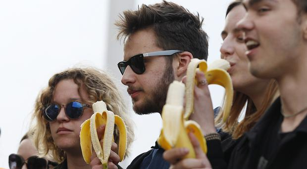 People with bananas demonstrate with others outside Warsaw's National Museum (Czarek Sokolowski/AP)