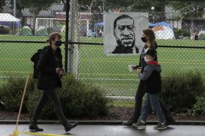 """People walk past an image of George Floyd on a fence around Cal Anderson Park inside what is being called the """"Capitol Hill Autonomous Zone"""" in Seattle (Ted S Warren/AP)"""