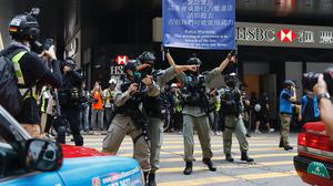 A riot police officer fires his weapon during a protest in Central Government Complex in the Central district of Hong Kong, Wednesday, May 27, 2020. Hong Kong police massed outside the legislature complex Wednesday, ahead of debate on a bill that would criminalize abuse of the Chinese national anthem in the semi-autonomous city. (AP Photo/Kin Cheung)