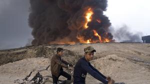 Youths ride bicycles next to a burning oil well i(AP)