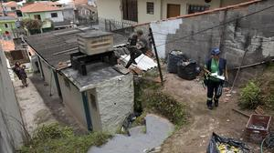 A soldier and a health agent check a Sao Paulo residence during an operation against the Aedes aegypti mosquito (AP)