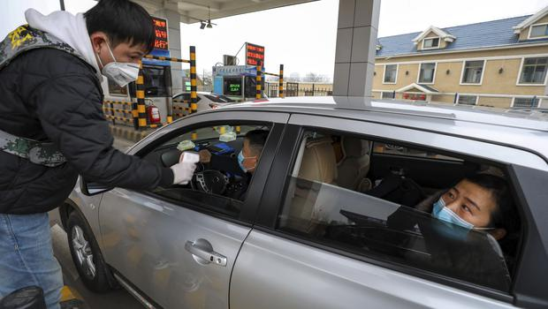 A militia member uses a thermometer gun to take a driver's temperature at a checkpoint at a highway toll gate in Wuhan (Chinatopix/AP)