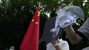 Pro-China supporters display a picture of US President Donald Trump during a protest against US sanctions (AP/Vincent Yu, File)
