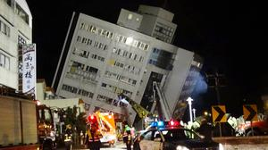 Rescuers are seen entering a building that collapsed onto its side from an early morning 6.4 magnitude earthquake in Hualien County, eastern Taiwan (Tian Jun-hsiung/AP)