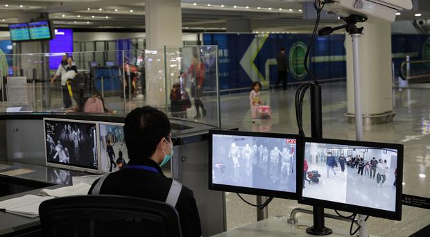 A health surveillance officer monitors passengers arriving at Hong Kong International airport. A preliminary investigation into viral pneumonia illnesses sickening dozens of people in and around China has identified the possible cause as a new type of coronavirus,(Andy Wong/AP)