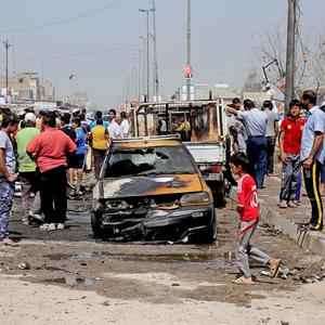 Civilians inspect the site of a car bomb attack in Baghdad's Sadr City neighbourhood (AP)