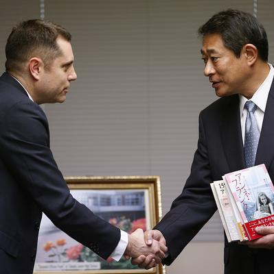 Israeli Embassy official Peleg Lewi, left, shakes hands with Suginami Ward Mayor Ryo Tanaka as he hands over Anne Frank-related books (AP)