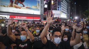 """Protesters singing and gesture with five fingers, signifying the """"Five demands – not one less"""" during a protest in Causeway Bay, Hong Kong, Friday, June 12, 2020. Protesters in Hong Kong got its government to withdraw extradition legislation last year, but now they're getting a more dreaded national security law, and the message from Beijing is that protest is futile. (AP Photo/Vincent Yu)"""