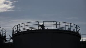 A worker is silhouetted on the top of a newly built water tank at the Fukushima Dai-ichi nuclear power plant in Okuma, Fukushima (AP)