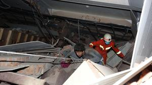 A man is assisted out from the rubble of a collapsed hotel building in Quanzhou (Chinatopix/AP)