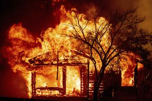 A home is engulfed by the flames (AP)