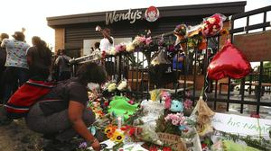 Tayla Myree sets out flowers on a shrine at a burned Wendy's (Curtis Compton/Atlanta Journal-Constitution via AP)