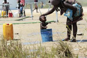 A mother bathes her baby in a bucket (Tsvangirai Mukwhazi/AP)
