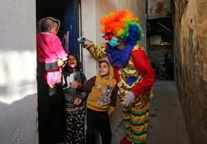 A Palestinian youth dressed as a clown and wearing protective gloves and mask puts on a show in the southern Gaza Strip