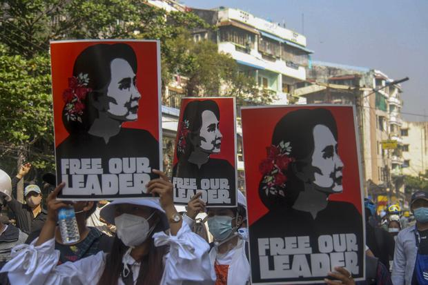 Anti-coup protesters display pictures of deposed leader Aung San Suu Kyi (AP)