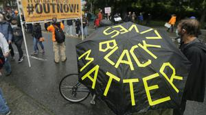 """A person holds an umbrella that reads """"Black Lives Matter"""" following a """"Silent March"""" against racial inequality and police brutality (Ted S. Warren/AP)"""