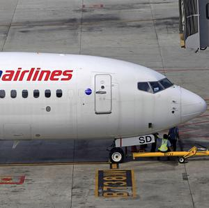 Ground staff take a break under a Malaysia Airlines plane at Kuala Lumpur International Airport (AP)