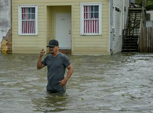 Barry Williams talks to a friend on his smartphone as he wades through storm surge from Lake Pontchartrain (Matthew Hinton/AP)