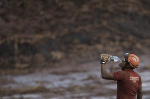 A firefighter drinks water as he works on a site where a body was found (Leo Correa/AP)