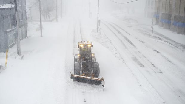 A snow plough clears a path through the snow in St John (Andrew Vaughan/The Canadian Press via AP)