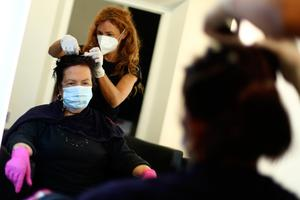 Italy: A young hairdresser and a customer wearing face masks and gloves to protect against the coronavirus in a salon in Brixen, Tyrol