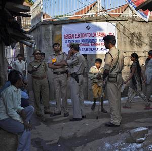 Policemen stand guard near a polling station in New Delhi (AP)
