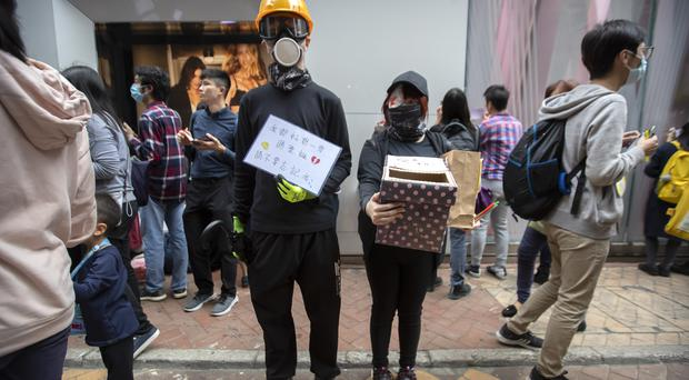 People hold a box to collect Christmas cards for detained and jailed protesters during a rally in Hong Kong on Monday (Mark Schiefelbein/AP)