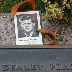 A photo of JKF and flowers lying on a plaque at Dealey Plaza in Dallas (AP)