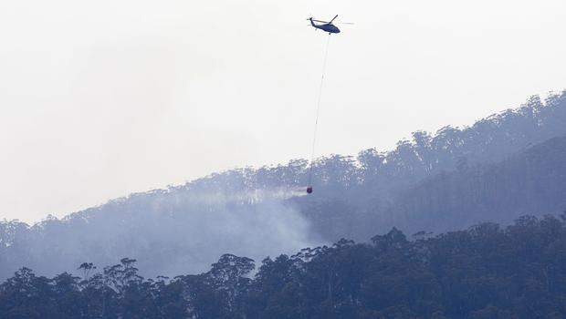 A helicopter prepares to drop water on a wildfire that burns in the hills near Cobargo, Australia (Rick Rycroft/AP)