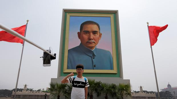 A man poses in front of a portrait of Sun Yat-sen, who is widely regarded as the founding father of modern China, in Tiananmen Square, Beijing (AP)
