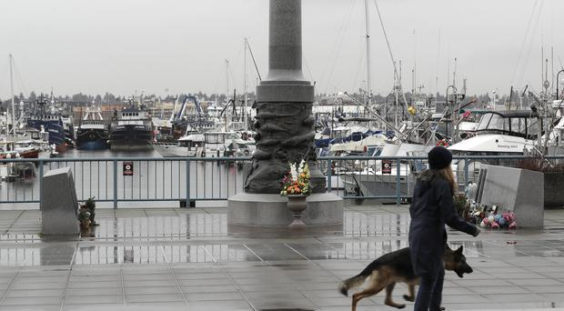 A woman and her dog pass the Seattle Fishermen's Memorial in Seattle on Thursday. Items left at the memorial included a baseball cap with the name of the crab fishing boat Scandies Rose, that sank on New Year's Eve. (Ted S Warren/AP)