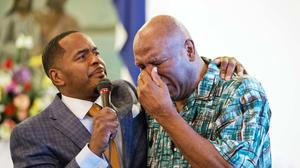Rahman Ali, brother of Muhammad Ali, right, cries while embraced by assistant pastor Rev. Charles Elliott, III