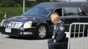 Police officers including Minneapolis Police Chief Medaria Arradondo, foreground, take a knee as the body of George Floyd arrives (Julio Cortez/AP)